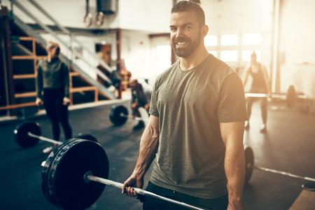 Colocar joven en ropa deportiva sonriendo mientras levanta pesas pesadas durante una sesión de entrenamiento en un gimnasio