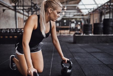 Fit young blonde woman in sportswear kneeling on a gym floor preparing to exercise with weights