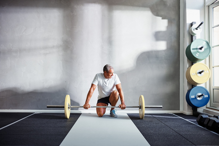 Senior man in sportswear kneeling kneeling in front of barbells while doing a workout in a health club