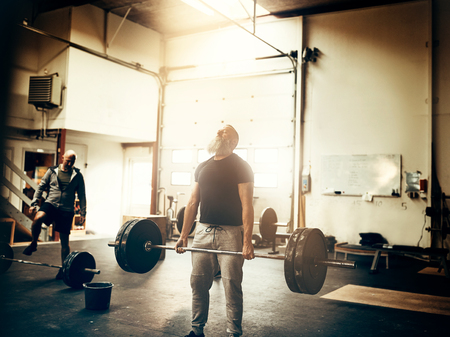 Fit mature man with a beard wearing sportswear straining to lift heavy weights while working out during a gym class