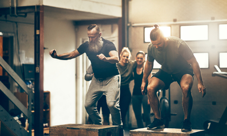 Two fit me doing box jumps during an exercise class in a gym with friends watching in the background