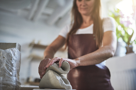 Female artisan standing alone in her creative ceramic workshop weighing pieces of clay on a scale
