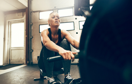 Fit young woman in sportswear exercising on a rowing machine during a gym workout session