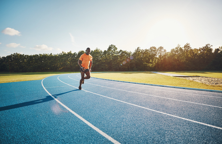 Focused young African male athlete in sportswear sprinting alone along a running track on a sunny day