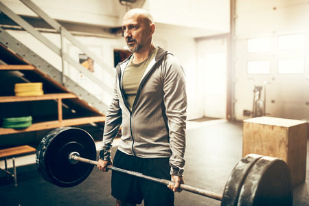 Fit mature man in sportswear standing alone in a gym lifting weights during an exercise session Stock Photo