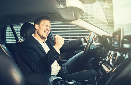 Young businessman in a blazer celebrating success with a fist pump while driving in a car during his morning commute 스톡 콘텐츠