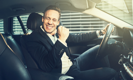 Young businessman in a blazer driving in a car during his morning commute and celebrating success with a fist pump