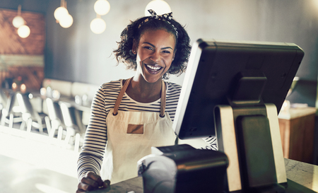 Young African waitress wearing an apron standing by a point of sale terminal and laughing while working in a trendy restaurant