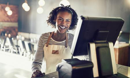 Junge afrikanische Kellnerin, die ein Vorfeld bereitsteht einen Verkaufspunktanschluß und ein Lachen beim Arbeiten in einem modischen Restaurant trägt
