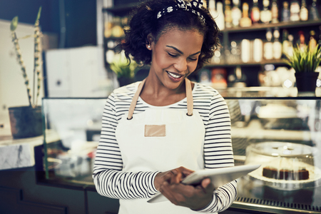 Young African entrepreneur in an apron standing in front of the counter of a trendy cafe working with a digital tablet