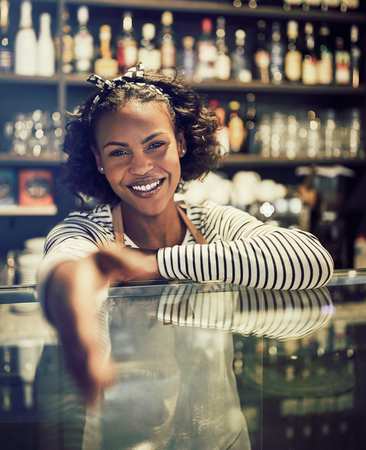 Young African entrepreneur smiling and extending a handshake while standing behind the counter of her trendy cafe