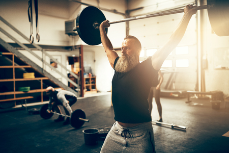 Fit mature man with a beard straining to lift weights above his head during a workout session in a gym