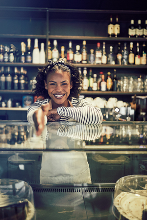 Young African entrepreneur smiling while standing behind the counter of her trendy cafe extending a welcoming handshake