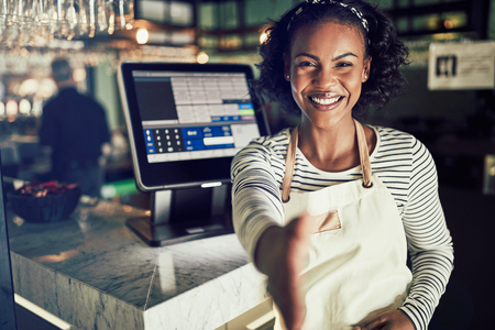 Smiling young African entrepreneur standing by a point of sale terminal in her restaurant extending a friendly handshake