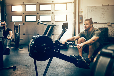 Fit young man in sportswear working out on a rowing machine during an exercise class in a gym Stock Photo