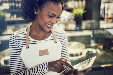 Smiling young African entrepreneur wearing an apron and using a digital tablet while standing in front of the counter of a trendy cafe
