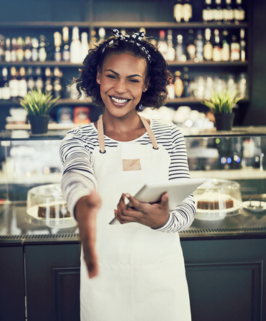 Smiling young African hostess extending her arm to shake hands while standing in a trendy cafe holding a digital tablet