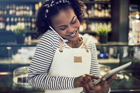 Smiling young African entrepreneur standing in her cafe taking cellphone reservations and using a digital tablet Stock Photo