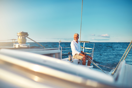 Smiling mature man sitting on the deck of his boat enjoying a sunny day sailing on the open ocean  Stockfoto