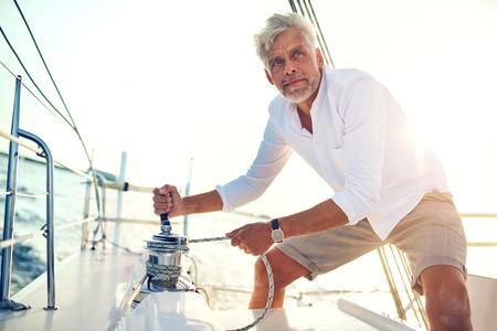 晴れた午後に航海するボートの甲板に立ちながらウィンチを働く成熟した男 写真素材