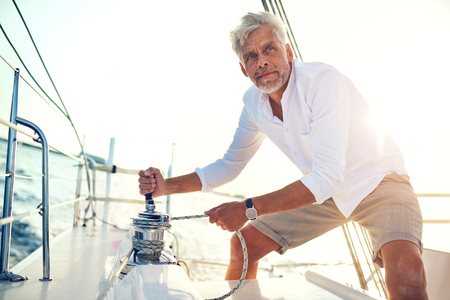 Mature man working a winch while standing on the deck of a boat sailing on a sunny afternoon Imagens