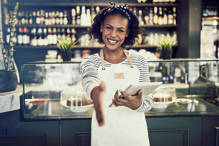 Smiling young African cafe owner extending a handshake while standing in a trendy cafe holding a digital tablet Stock Photo