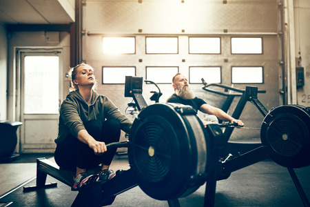 Two fit people in sportswear working out together on rowing machines during an exercise session at the gym Stock Photo