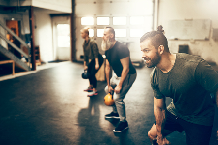 Fit group of people working out with dumbbells together during an exercise class at a gym Фото со стока