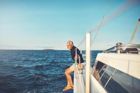 Smiling mature man leaning on the railing of his boat while enjoying a day sailing on the ocean