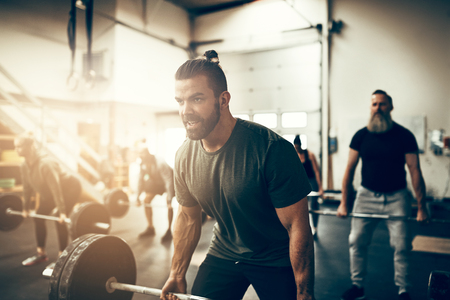 Fit young man in sportswear straining to lift heavy weights while working out during a gym class Stock Photo
