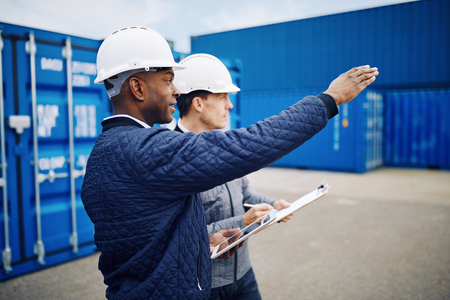 Two engineers wearing hardhats standing on a large commercial shipping dock tracking inventory together