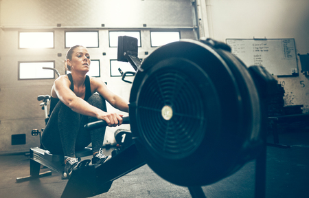 Fit young woman exercising on a rowing machine during a workout session at the gym