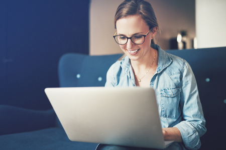 Smiling young female entrepreneur browsing online with a laptop while sitting on her sofa working from home