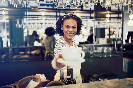 Smiling African barista standing behind the counter of a trendy cafe holding up a fresh cup of coffee Banco de Imagens