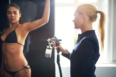Professional beautician applying liquid tan on female client hip with aerograph. Stock Photo