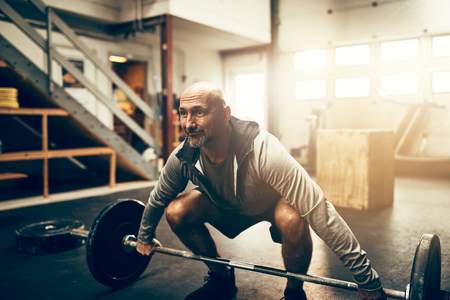 Focused mature man in sportswear preparing to lift weights while working out alone in a gym