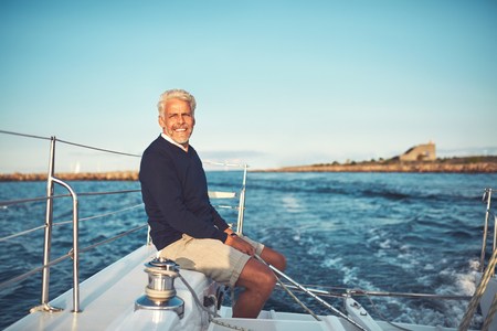 Smiling mature man sitting alone on the deck of his boat sailing along the coastline on a sunny afternoon