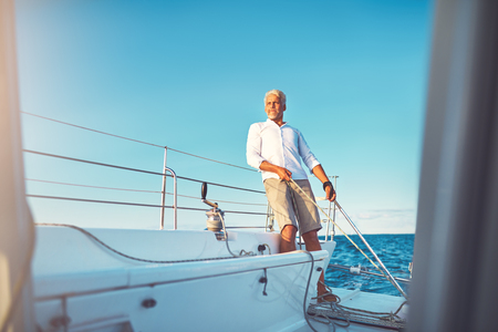 Mature man standing on the deck of a boat steering with the rudder while out for a sail on the ocean on a sunny day