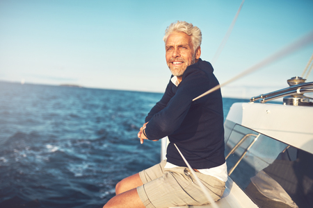 Smiling mature man enjoying the view from the deck of his boat while out sailing on the open ocean