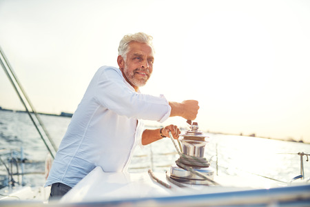 Smiling Mature man standing on the deck of a boat winding a winch while enjoying a sunny afternoon sailing on the ocean Stok Fotoğraf