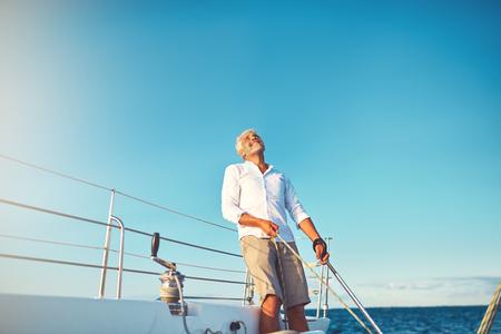晴れた日に出航中にリギングを見上げるボートデッキに立つ成熟した男