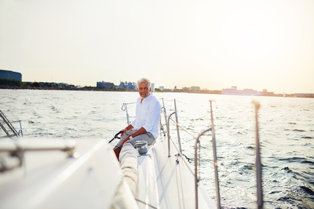 Mature man sitting alone on the deck of a boat sailing along the coast on a sunny day