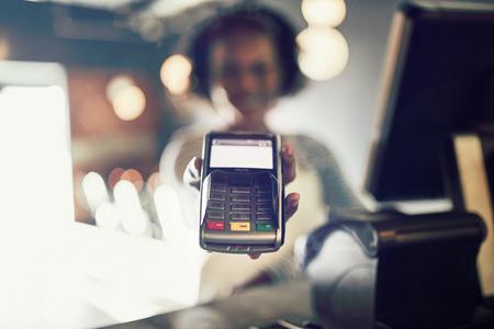 Joven camarera africana sosteniendo una máquina de pago con tarjeta electrónica mientras está de pie junto a un terminal de punto de venta en un restaurante de moda Foto de archivo