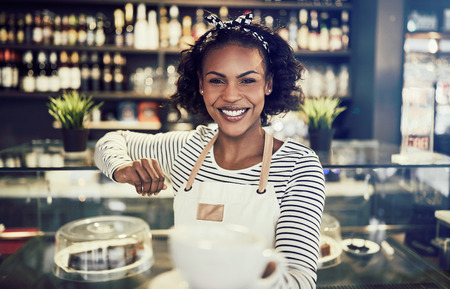 Smiling African barista leaning on the counter of a trendy cafe holding up a fresh cup of coffee