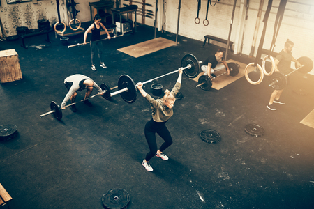 High angle of a group of fit people lifting weights together during an exercise class at a gym