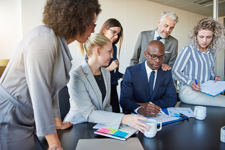 Diverse group of businesspeople reviewing paperwork together while having a meeting around a boardroom table in a modern office