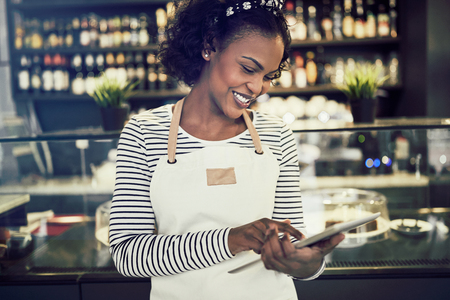 Young African entrepreneur wearing an apron standing in her trendy cafe working with a digital tablet