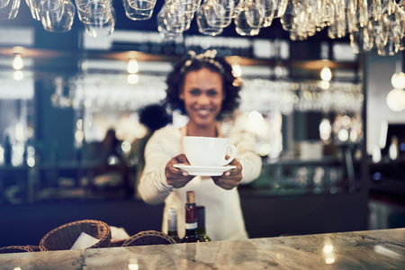 Smiling young African barista standing alone behind the counter of a trendy cafe holding up a cup of freshly brewed coffee Stock Photo