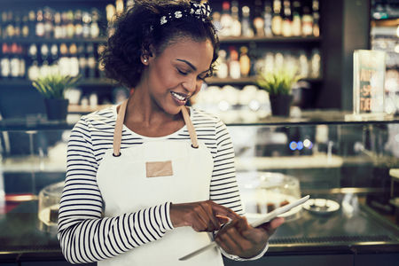 Smiling African entrepreneur wearing an apron using a digital tablet while standing in front of a counter of her trendy cafe