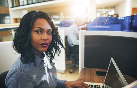 Portrait of an attractive young businesswoman looking focused while sitting at a cubicle in a modern office building working online with a laptop